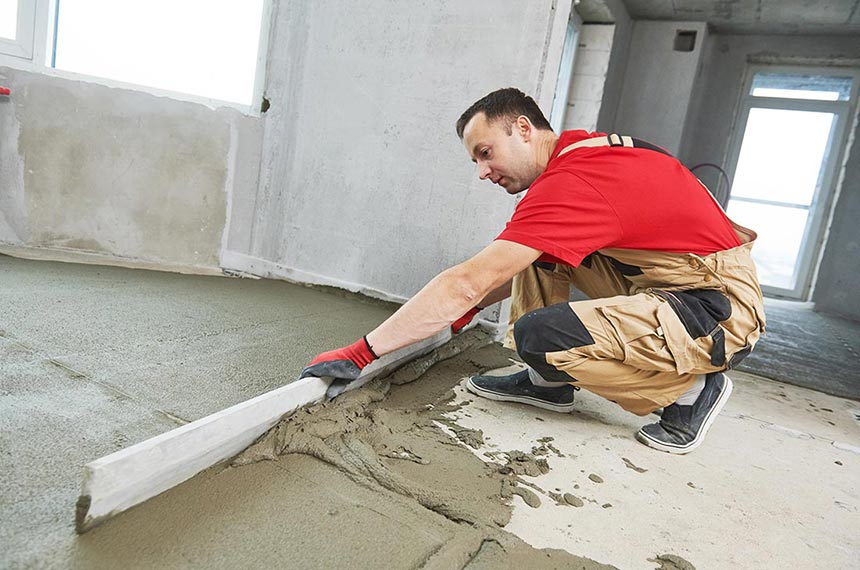 Plasterer smoothing floor surface with a screeder during concrete floor preparation