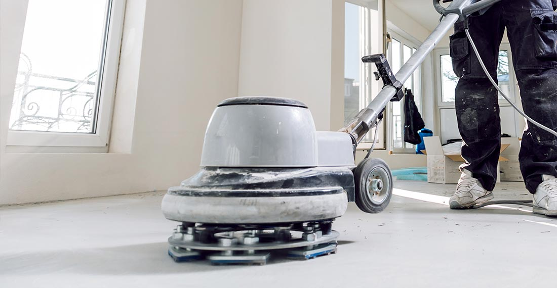 Worker using a concrete grinder during concrete floor preparation in Perth