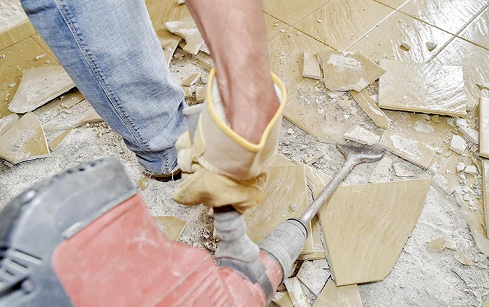 Worker smashing floor tiles to get ready for a new polished concrete floor