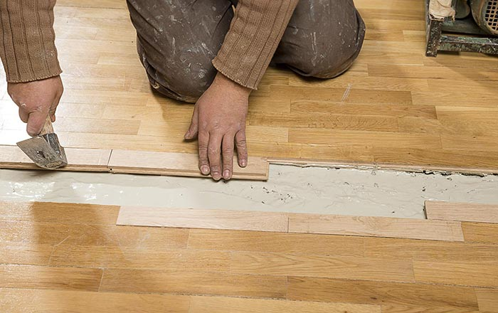 Worker preparing a concrete surface by removing timber flooring